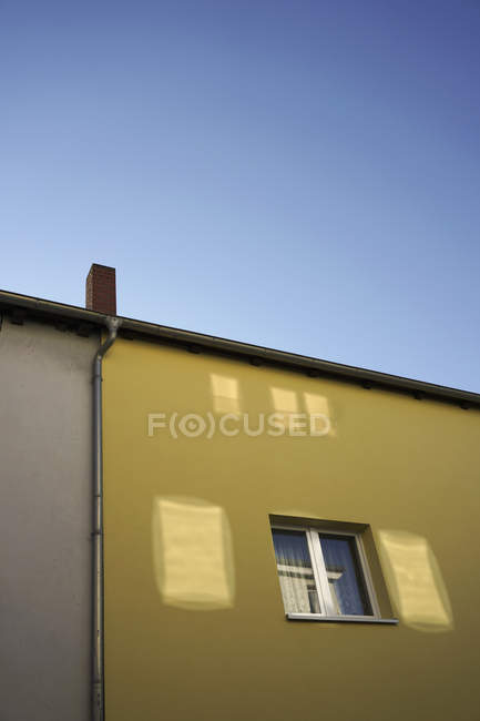 Low angle view of yellow residential building against clear blue sky — Stock Photo