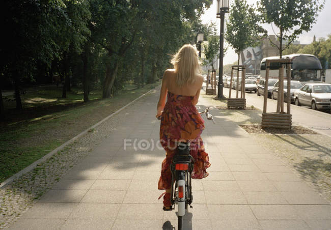 Rear view of blonde woman riding bicycle on footpath — Stock Photo