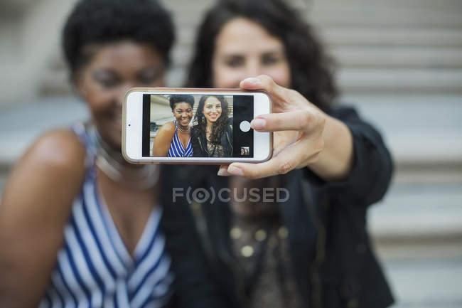 Femme prenant selfie avec jeune amie avec téléphone portable — Photo de stock