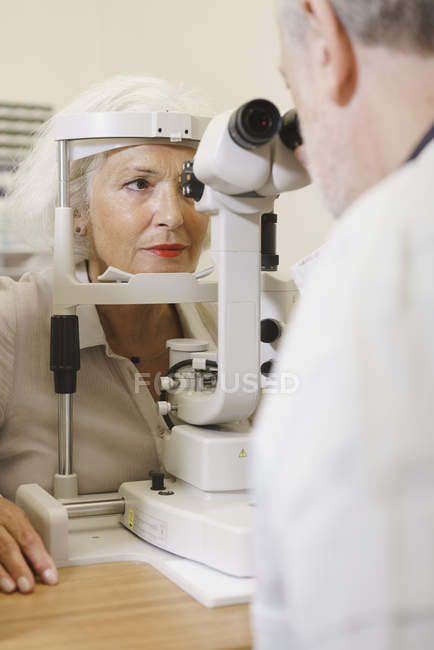 Doctor examining senior womans eye in clinic — Stock Photo