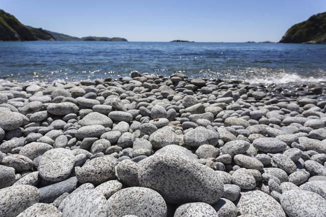 Superfície vista nível de pedras do seixo na praia na praia — Fotografia de Stock