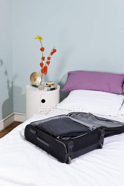 Packed suitcase on white bed — Stock Photo