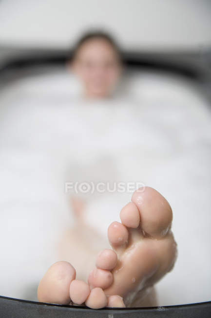 Woman lying in bathtub with feet resting on the edge — Stock Photo