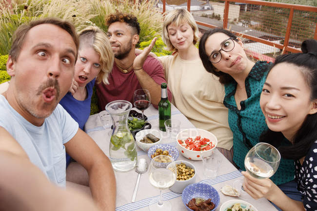 Portrait of playful friends making faces while sitting at outdoor table at patio — Stock Photo