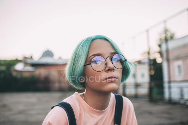 Ritratto di adolescente con capelli tinti di verde che indossa occhiali — Foto stock