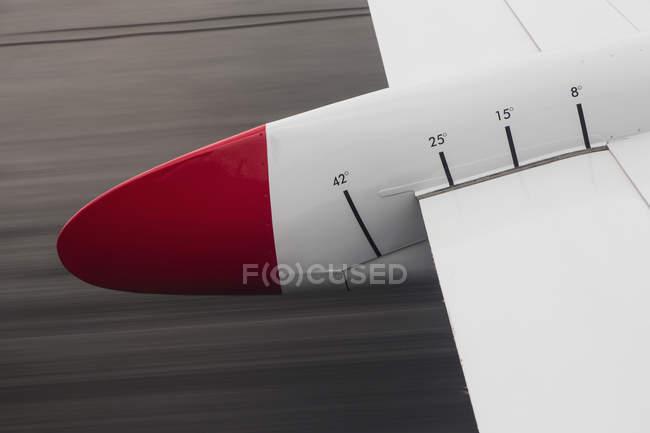 Imagem recortada de asa de avião vermelho e branco com números — Fotografia de Stock