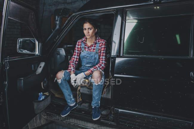 Портрет уверенной женщины-механика, сидящей в машине в мастерской — стоковое фото