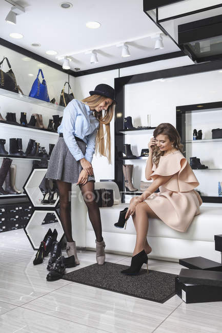 Feliz amigos do sexo feminino experimentando sapatos na loja — Fotografia de Stock