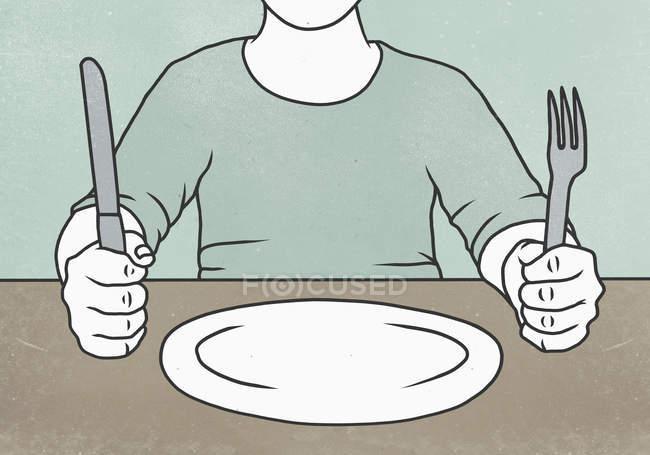 Midsection de homem segurando garfo e faca à mesa com placa vazia — Fotografia de Stock