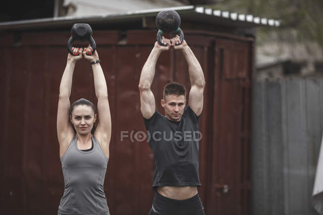 Male and female athletes exercising with kettlebells during crossfit training — Stock Photo