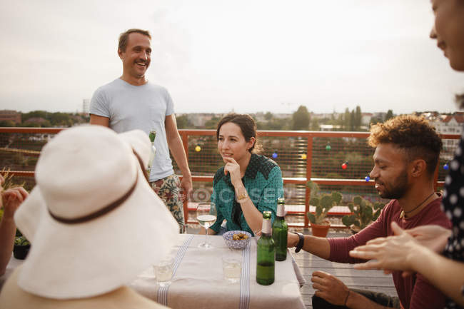 Happy male and female friends enjoying at outdoor table on patio — Stock Photo