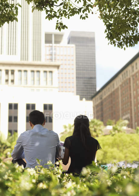Rear view of businessman and businesswoman sitting side by side in downtown park — Stock Photo