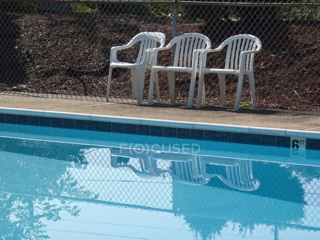 Три пластиковых стула на открытом воздухе на краю бассейна — стоковое фото