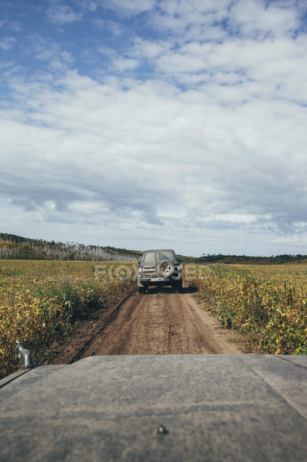Off-road vehicle moving on dirt road amidst plants in field against sky, Svobodniy, Amur, Russia — Stock Photo