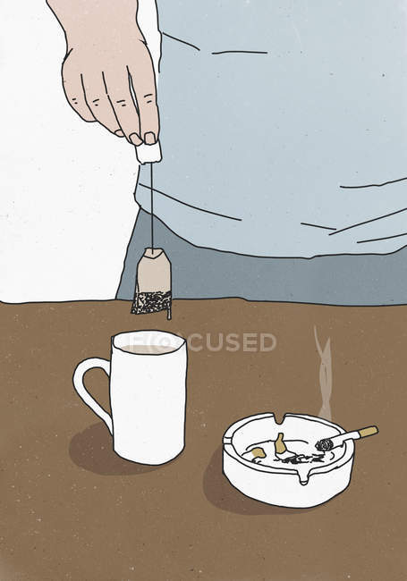Hand holding teabag above cup by ashtray on table — Stock Photo