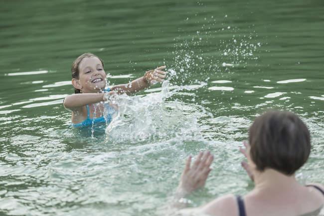Grandmother and granddaughter splashing water in lake — Stock Photo