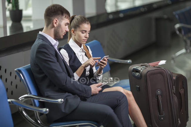 Young business couple using mobile phones while waiting at airport — Stock Photo