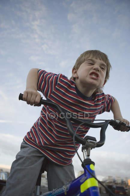 Jeune garçon faisant face à vélo — Photo de stock