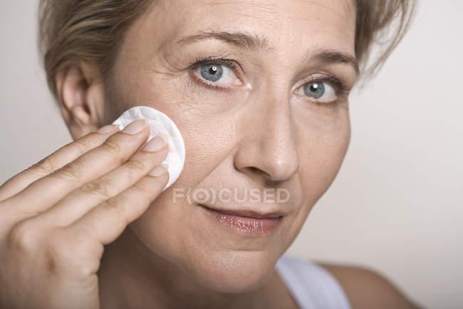 Femme, nettoyage visage avec une serviette en coton — Photo de stock