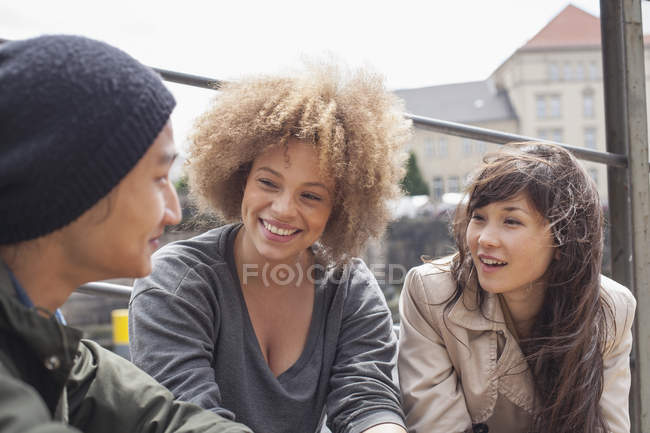 Smiling young friends talking while sitting on sunny day — Stock Photo