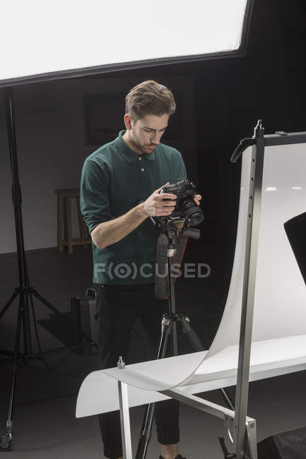 Confident photographer looking at backdrop while working in studio — Stock Photo