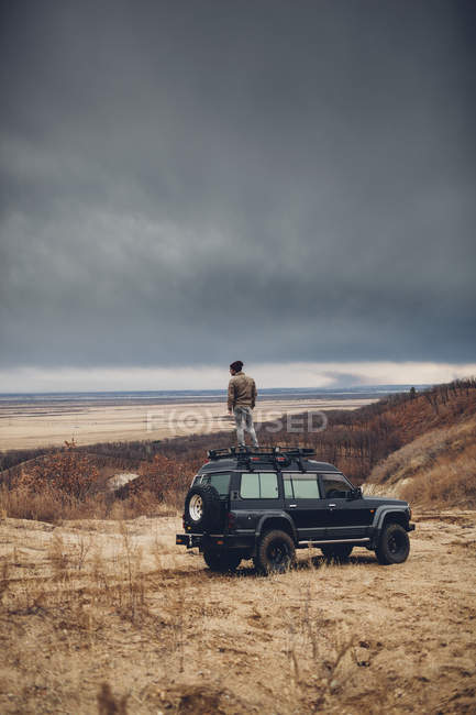 Man standing on top of sports utility vehicle over land against cloudy sky, Amur, Russia — Stock Photo