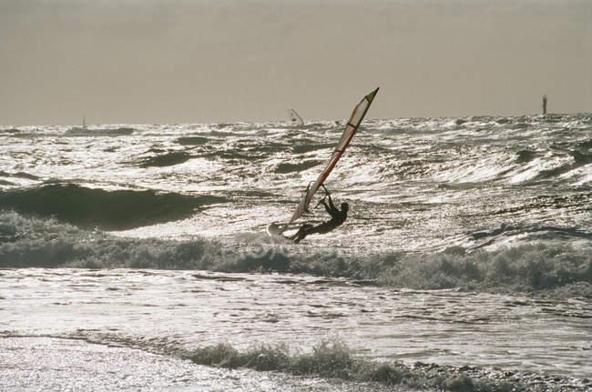 Vista distante da pessoa windsurf nas ondas do oceano — Fotografia de Stock