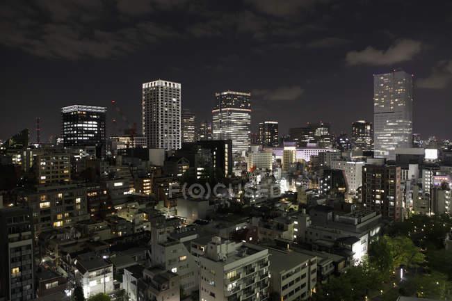 Bâtiments illuminés en ville dans le ciel de nuit — Photo de stock