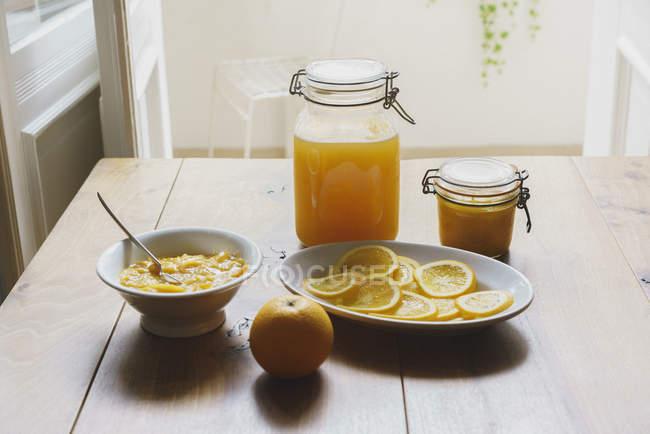 Natura morta di agrumi salse e conserve sul tavolo — Foto stock