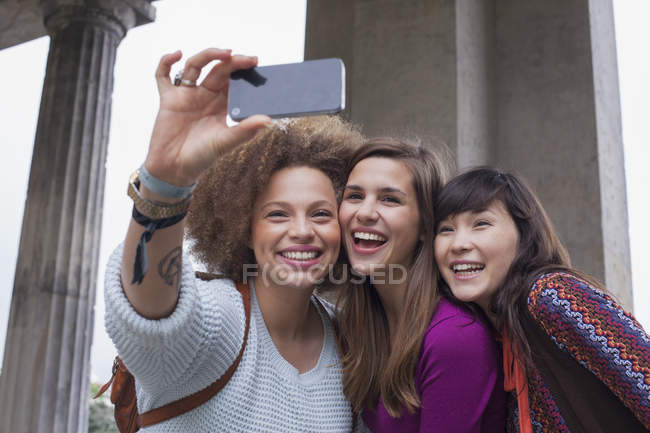 Low angle view of smiling young female friends taking selfie — Stock Photo