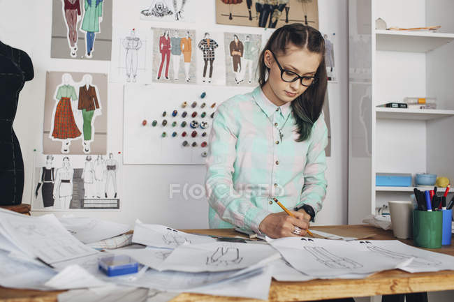 Fashion designer drawing sketches at workbench in studio — Stock Photo