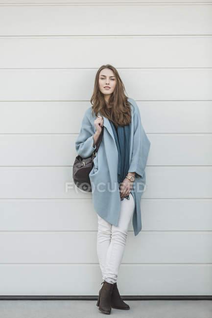 Портрет молодої жінки з рюкзака стоячи перед стіни — стокове фото