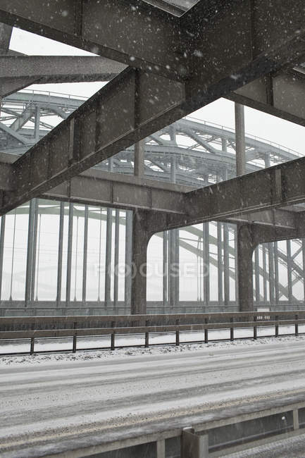Metal structure of road bridge in snowstorm — Stock Photo