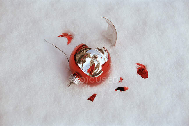 Shattered Christmas bauble decoration in snow — Stock Photo