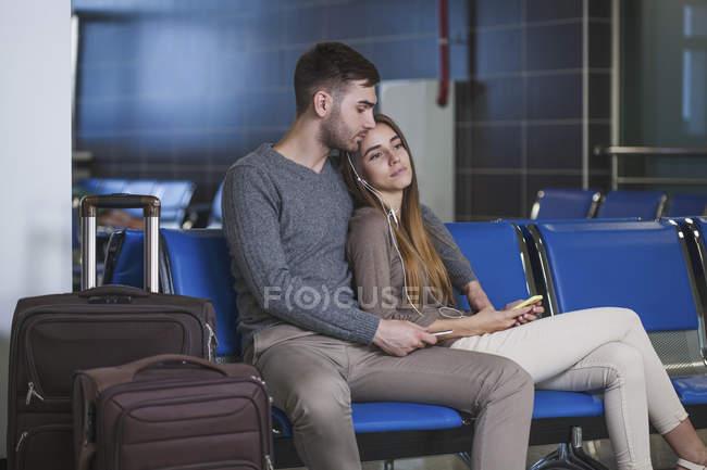 Молоді пара прослуховування музики через мобільний телефон під час очікування в аеропорту — стокове фото