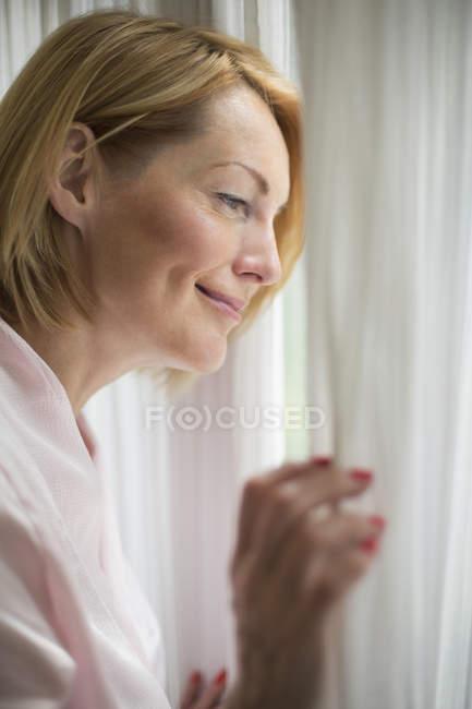 Donna sorridente che indossa accappatoio guardando attraverso la finestra in bagno — Foto stock