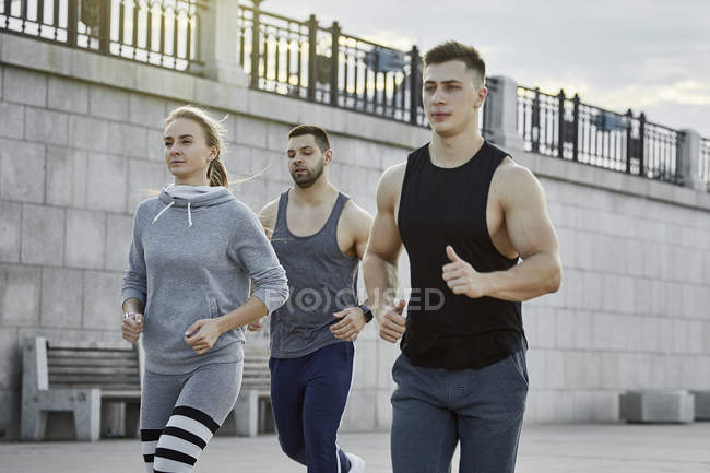 Young athletes jogging against bridge — Stock Photo