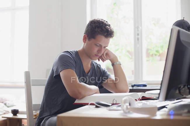 Молодой студент университета, обучающийся дома — стоковое фото