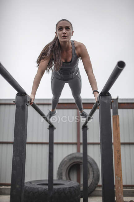 Female athlete doing push-ups on parallel bars during crossfit training — Stock Photo