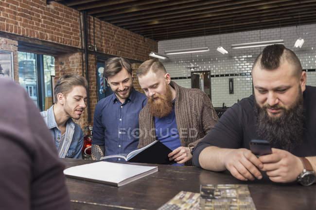 Cabeleireiros masculinos felizes no balcão de bar na barbearia — Fotografia de Stock