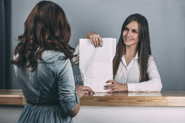 Young saleswoman handing over bag to female customer in store — Stock Photo