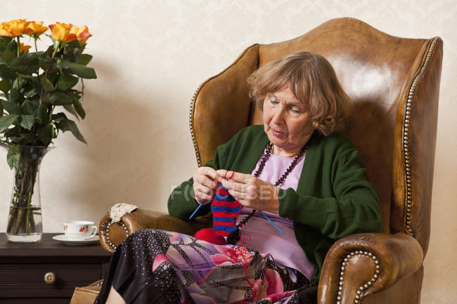 Focused senior woman knitting in armchair at home — Stock Photo