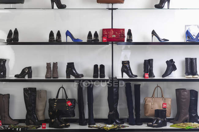 Various shoes and purses displayed on shelves at store — Stock Photo