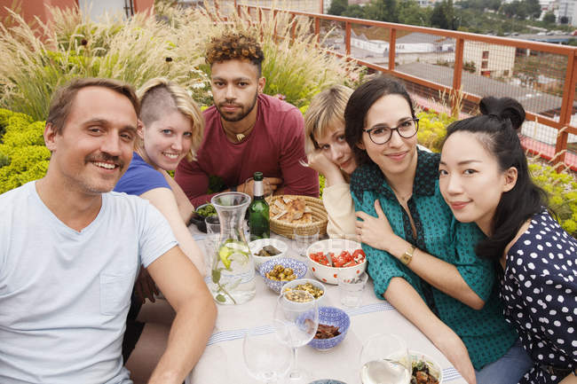 Portrait of happy male and female friends sitting at outdoor table at patio — Stock Photo