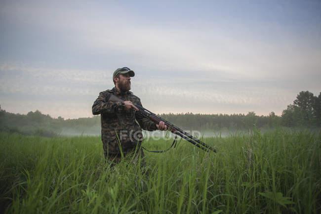 Rifle de cazador cartera estando en el campo contra el cielo - foto de stock