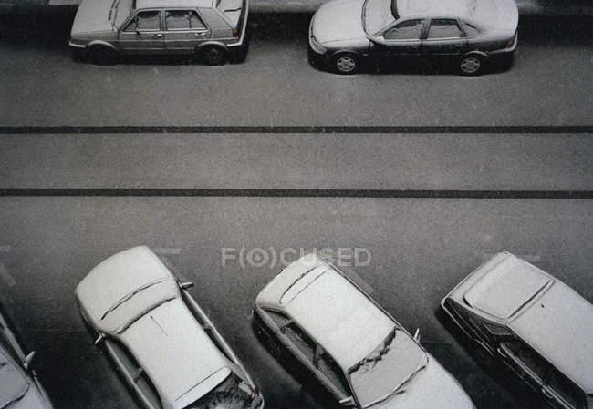 Сверху припаркованные на улице вагоны покрыты снегом — стоковое фото