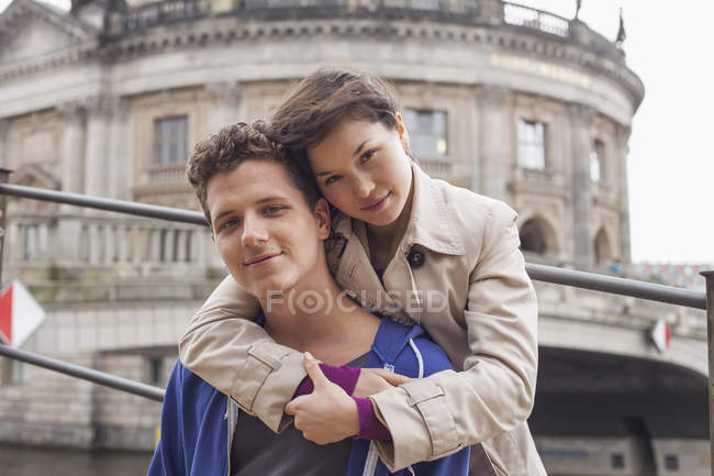 Low angle portrait of woman embracing male friend against Bode Museum, Berlin, Germany — Stock Photo