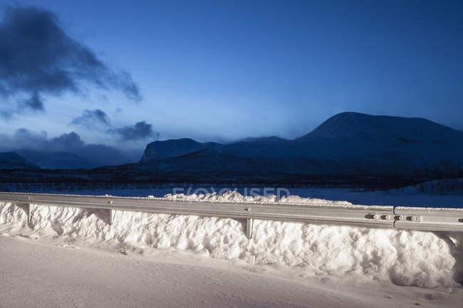 Railing on snow covered mountains against blue sky at night, Nikkaluokta, Sweden — Stock Photo