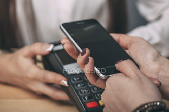 Detail image of woman using smart phone to pay at counter — Stock Photo