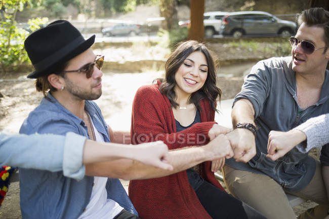 Cheerful male and female friends doing fist bumps in park — Stock Photo